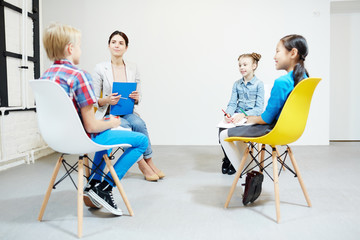 Little schoolgirls and young teacher listening to report of clever boy at seminar