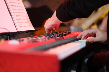 A musician on an electric piano plays live music at a concert in an orchestra