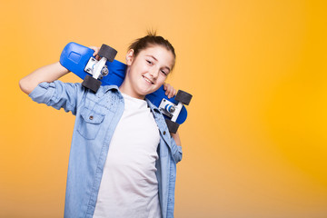 Happy teenager girl with her blue skateboard on shoulders on yellow background