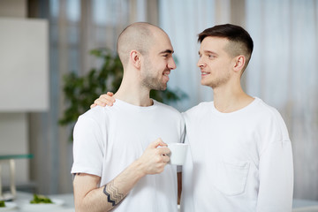Two amorous gay men looking at one another while one of them having coffee in the morning