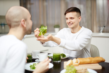 Young man giving his partner fresh lettuce during breakfast in the kitchen