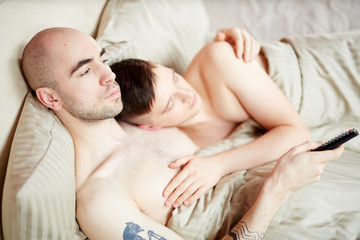 Gay couple lying in bed and watching television broadcast in the evening