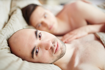 Bald guy lying in bed with his head on pillow and looking at camera with his partner on background