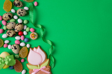 Easter quail Eggs and Candy on side of green Background with blank room or space for copy, text, your words. Vertical aerial top view