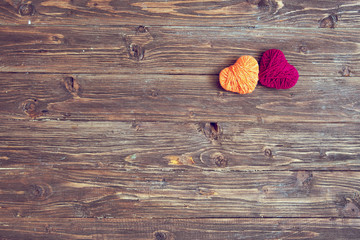 Two heart shape of yarn on vintage wooden background