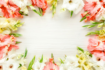 Floral frame made of pink, white gladioluses on wooden white background. Pattern of gladioli with space for your text, holiday greeting card. Valentine's. Flat lay, top view. Flowers texture