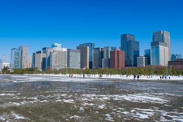積雪の皇居前広場と高層ビル群