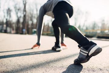 Male athlete prepares to run in autumn park
