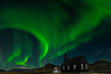 Northern Lights over The Black Church Budir, Iceland. Aurora Borealis in an amazing nightscape. Travel destination with beautiful green lights landscape.