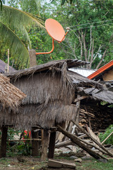 a modern satellite dish on the roof of shack in hmong village, Laos. Traditional house in the hmong tribe village.