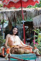 young woman in traditional Thai clothes sits on the historical litter. Thai girl in the historical costume relaxed under umbrella.