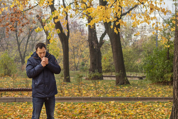Handsome man walking in the autumn park. Man smoking cigarette in outdoor. Bad habit.
