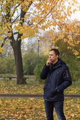 Handsome man walking in the autumn park. Man smoking cigarette in outdoor. Bad habit.