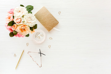 Women's workspace with pink and beige roses flowers bouquet, accessories, diary, glasses on white background. Flat lay, top view trendy fashion feminine background. Beauty blog concept.