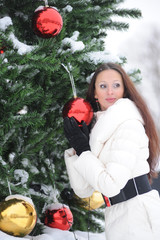 beautiful brunette in winter at christmas tree with red christmas balls