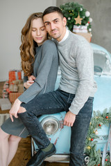 Young couple sitting on retro car in Christmas decorated studio