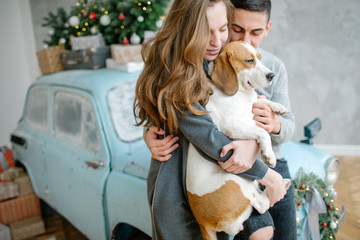 Young couple with beagle and retro car in decorated studio