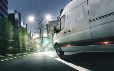 Lieferwagen fährt in beleuchteter Stadt