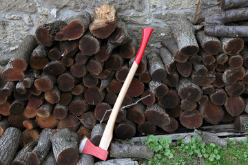 red ax and wood stack near a village house