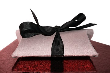 Isolated gift box with black ribbon on red glittery pad background