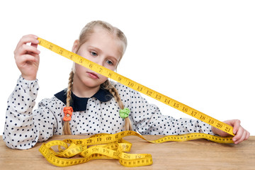 Little girl sitting at a wooden table studying measuring tape measure isolated on a white background