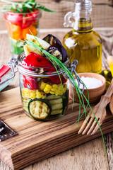Grilled summer vegetables in glass jar