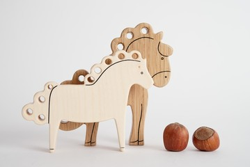 Wooden hand-made horse toy for children isolated on the white background with shadow reflection. Wooden acorn for playing with kids. Natural typical wooden toy in the shape of little horse