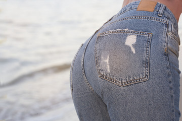 Sexy perfect woman in jeans against the sea. back view. Middle body parts. Fashion. Advertising of fashionable jeans.