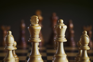 Detail of wooden white chess figures, dark background
