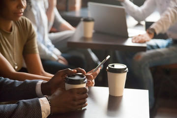 Coffee break in cafe with gadgets concept, diverse young african and caucasian people sitting at coffeehouse tables with drink to go in paper cups enjoy using mobile phone and laptop, close up view
