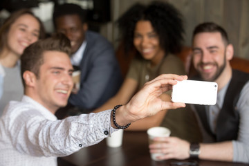 Taking group selfie concept, multiracial african and caucasian young friends making photo on modern smartphone camera at meeting, smiling man holding cell shooting video, focus on phone, close up