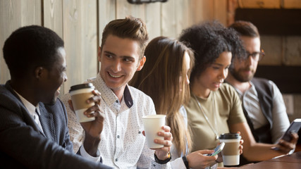 Multiracial young men talking and drinking coffee while other friends using gadgets at meeting in coffeehouse, smiling mates enjoying conversation having fun sitting at cafe table with diverse people