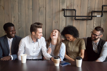 Young man joking at cafe meeting making multiracial friends laugh, diverse people guffaw after guy telling funny comic story during coffee break, happy black and white mates having fun in coffeehouse