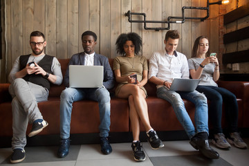 Diverse young people sitting in row on couch together obsessed with devices online, african and caucasian millennial addicts using laptops and smartphones, digital life and gadgets overuse concept