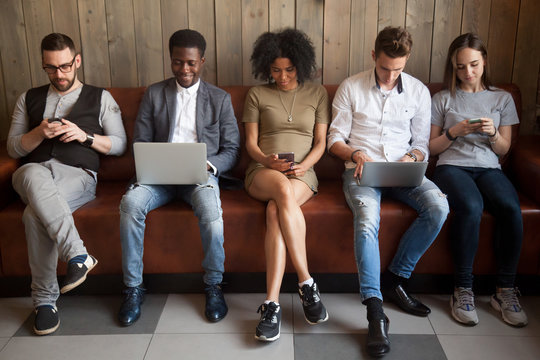 Multicultural young people using laptops and smartphones sitting in row, diverse african and caucasian millennials entertaining online obsessed with modern devices waiting in queue, gadget addiction