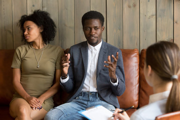 African man talking to family counselor, frustrated husband sharing marital problems while offended wife sitting silent on couch, black unhappy couple visiting psychologist, marriage counseling