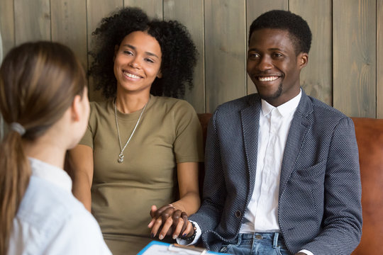 African american young couple holding hands happy to hear good news from doctor, black husband and wife feel relieved after reconciliation during therapy session listening to family marriage counsel