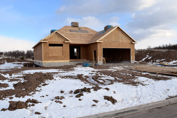 New Home Under Construction in Winter with Lumber Framing and Carpentry Builders Roofing Craftsman
