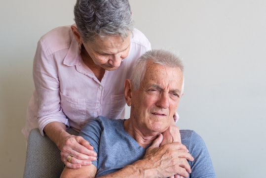 Older man looking concerned and being comforted by older woman (selective focus)