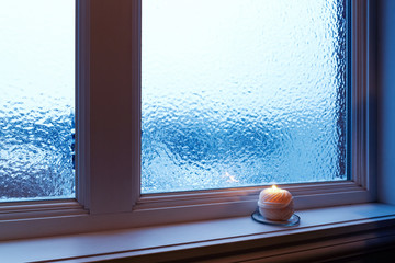 Cozy candle burning near a frosted window