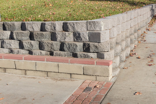 Residential retaining wall featuring a variety of stacked blocks and mortared brick textures, horizontal aspect