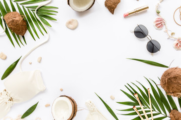 Wall Mural - Feminine beige swimsuit beach accessories, tropical palm leaf branches, coconuts on white background with empty space for text. Summer background. Traveler accessories. Flat lay, top view.