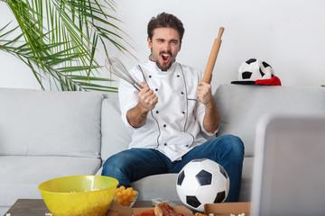 Young man chef sport fan watching match goal