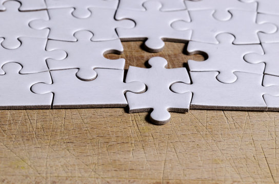the unexpected solution, white jigsaw/puzzle with one piece at wrong position, over  black wooden table background, symbol of problem solving and new vision