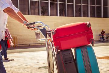 Mann schiebt Gepäckwagen mit drei Koffern