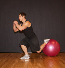 muscular sportsman doing exercise lunges with fitball in gym interior