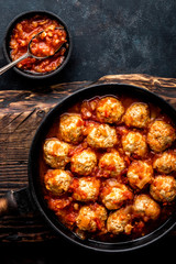 Homemade meatballs stewed in tomato sauce in cast iron pan