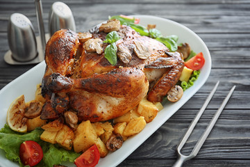 Delicious whole roasted chicken served on wooden table