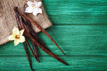 Vanilla sticks and flowers on wooden background