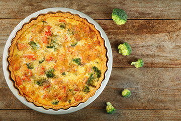Baking dish with tasty broccoli quiche on table